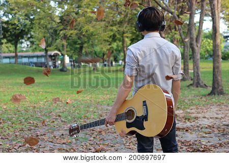 Back view of relaxed young man with headphones is holding acoustic guitar and falling leaves in outdoor park.