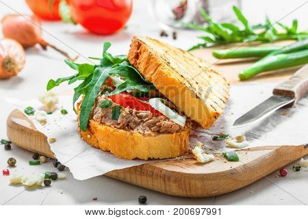 Classic tuna salad sandwich with tomato onion and arugula on a white table. Delicious healthy meal made of fish vegetables and toasts.