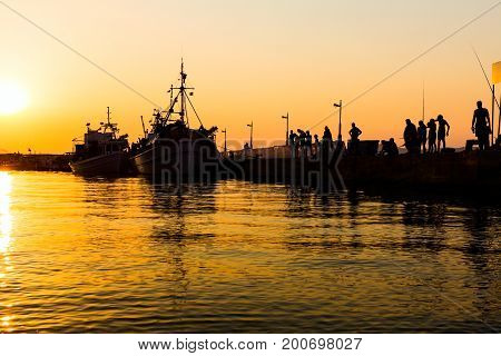Silhouettes of fishers until they are fishing on the dock at sunset.