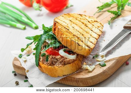 Grilled sandwich with tuna salad tomato onion and arugula on a white wooden table. Diet healthy finger food made of toasts vegetables and fish.