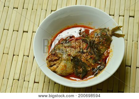spicy climbing gourami fish dried red curry paste with basil on bowl