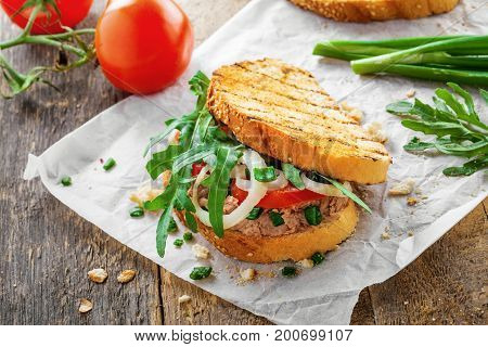 Delicious sandwich made of toasts tuna tomato onion and arugula with ingredients on a table. Traditional healthy food.