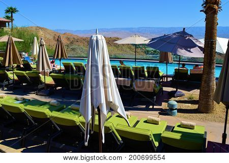 August 9, 2017 in Palm Desert, CA:  Contemporary style furniture including lounge chairs, tables, and umbrellas surrounding a luxury pool taken at the Ritz Carlton Hotel where guests can swim and sunbathe by the luxurious pool in Palm Desert, CA