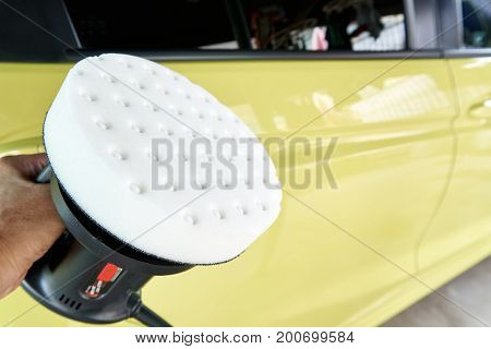 car detailing of worker's hand using polishing and waxing in garage with copy space on the right