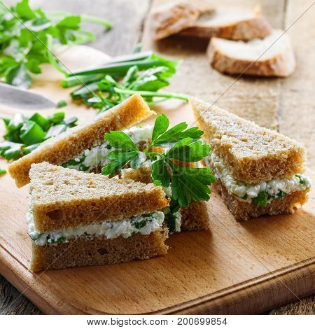 Delicious sandwiches made of rye bread cream cheese fresh parsley and green onion on a rustic table. Simple homemade appetizer.
