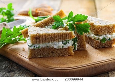 Sandwiches made of rye bread cream cheese green onion and fresh parsley on a rustic table. Delicious healthy appetizers. Close-up shot.