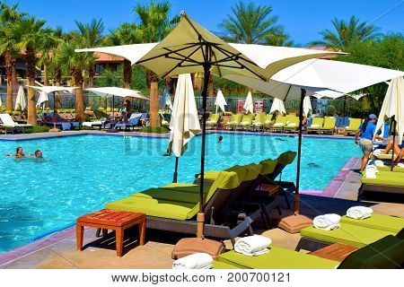 August 9, 2017 in Palm Desert, CA:  Contemporary style furniture including lounge chairs, tables, and umbrellas surrounding a pool taken at the Ritz Carlton Resort where guests can swim and relax by the luxury pool