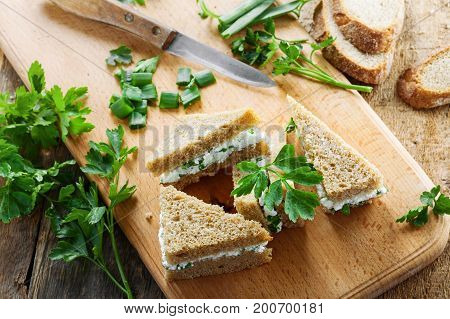 Healthy simple snack made of rye bread cream cheese fresh parsley and green onion on a table. Delicious small sandwiches. Top view.