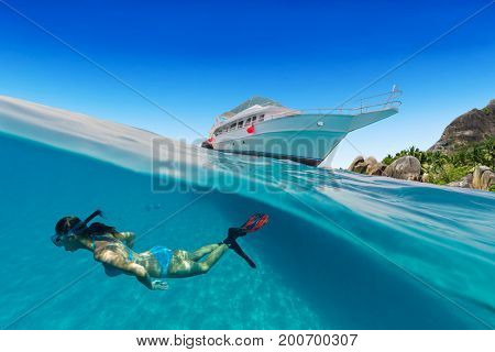 Small safari boat with snorkeling woman underwater. Beautiful split shot under and above water. Travel lifestyle, water sport outdoor activities, swimming and snorkeling