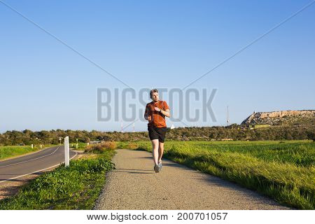Man running outdoor sprinting for success. Male fitness runner sport athlete in sprint at great speed in beautiful landscape