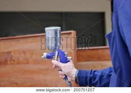 Hands of industrial worker holding spray paint gun in the factory.