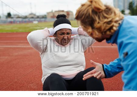 Determined plus-sized woman doing difficult exercise with her trainer help