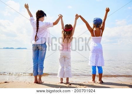 Back view of three ecstatic girls holding by hands while raising them in front of the sea
