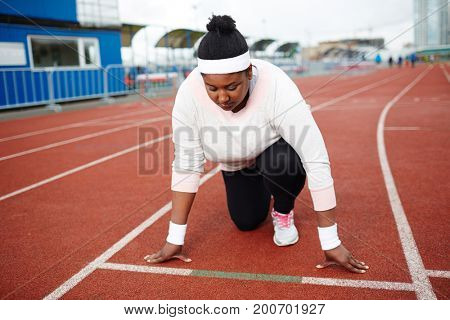 Young overweight woman standing by start line on racetrack ready to run