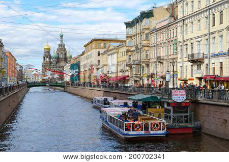 SAINT PETERSBURG RUSSIA - MAY 3 2017: Unknown people are walking along embankment of Griboyedov Canal St. Petersburg Russia