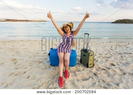 Happy laughing woman tourist with suitcases standing near the sea. Travel and summer vacation concepts.