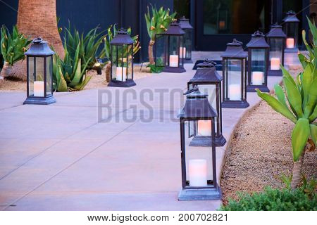Walkway with lit rustic Southwestern style lamps surrounded by a cactus and rock garden taken in a residential yard poster
