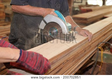 Senior carpenter is cutting a piece of wood with electric circular saw in carpentry workshop.