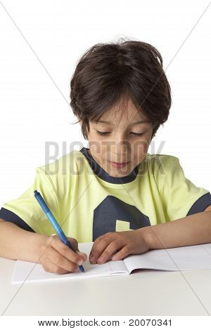 Little boy is writing in his notebook