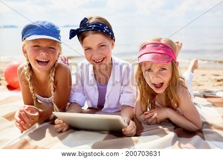 Ecstatic friendly girls with tablet having fun on sandy beach