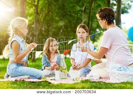 Kindergarten teacher shaming little girls during picnic or outdoor party in park