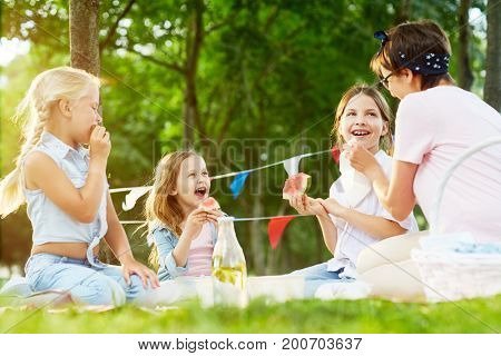 Cheerful girls and their teacher relaxing on green grass in park