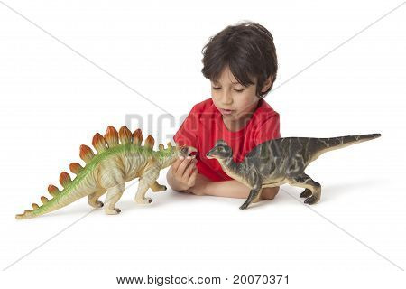 Little boy is playing with toy dinosaurs