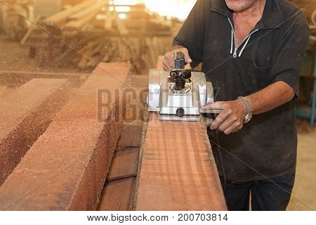 Selective on electric planer is being worked with senior carpenter in carpentry workshop. Shallow depth of field.