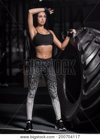 Powerful attractive muscular girl engaged in training with giant tires in the gym. Athlete resting after a hard workout. Exercise with heavy weight in the gym.