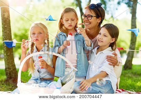 Little girls blowing soap-bubbles during picnic with kindergarten teacher or mother