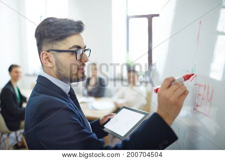 Business analyst drawing graph on whiteboard while preparing for seminar