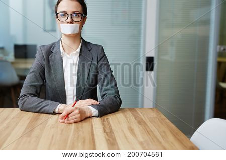 Voiceless busineswoman with her mouth stuck sitting by workplace