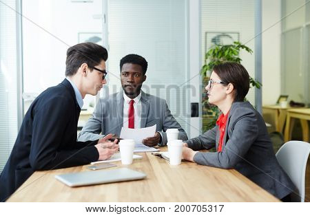 Group of employees discussing financial situation at meeting in boardroom