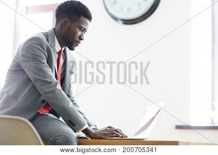 Elegant businessman concentrating on network in office