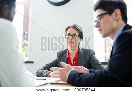 Confident employers talking to applicant at interview