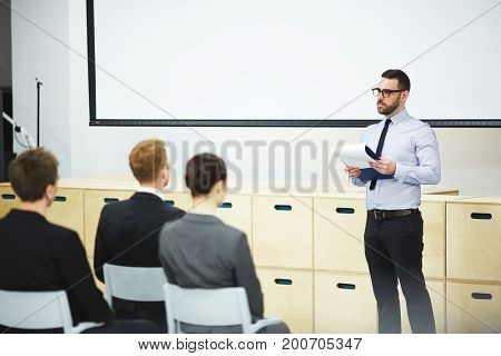 Confident young speaker presenting his point of view concerning company development while participating in business conference