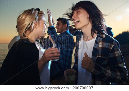 Laughing young couple with glasses of cocktails and their friends dancing at sunset on the beach