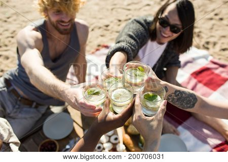 Young people toasting with glasses of mojito cocktail at beach party