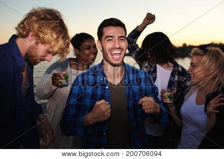 Ecstatic dancers enjoying summer evening by seaside