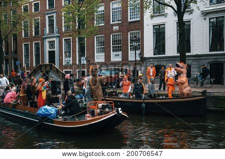 Amsterdam Netherlands - 27 April 2017: Local people and tourists dressed in orange clothes and funny costumes ride on boats and participate in celebrating King's Day along the canal of Amsterdam.