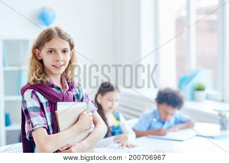 Elementary youngster with copybooks and his classmates on background