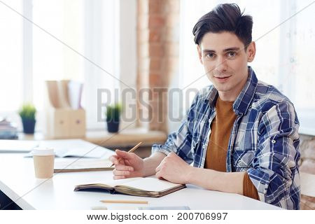 Confident young man with pencil and notebook planning work or writing down project points