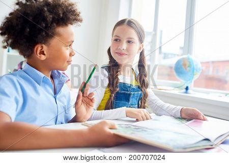 Schoolboy explaining to his classmate what he read in the book