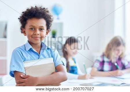 Cute schoolboy with copybook looking at camera with his classmates on background