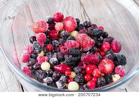 Frozen berries in a glass bowl on a wooden background