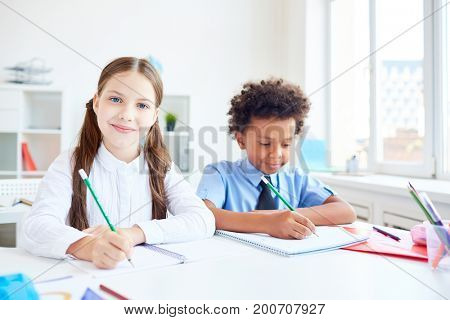 Two school friends drawing in copybooks at lesson