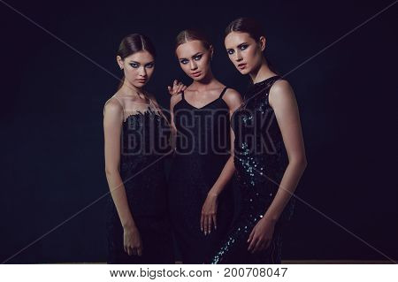 Beautiful women in black cocktail dresses on a dark background.