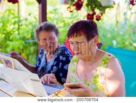 Senior woman in terrace trying to talk with her busy girlfriend concentrating on her notebook and smartphone.