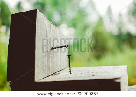 Screw screwed into a wooden Board on green background