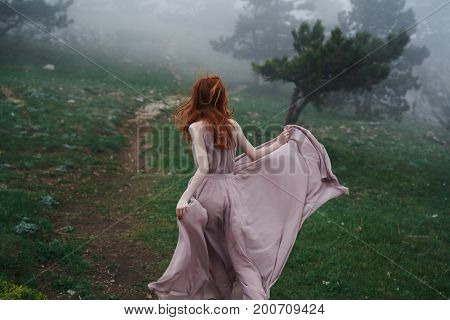 Beautiful young woman in a long dress in the mountains by the forest.